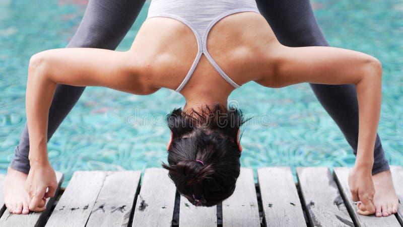 Poserar den yrkesmässiga asiatiska krökningen för följden för kvinnaövningsyoga lade benen på ryggen framåt sneda bollen arkivfoto
