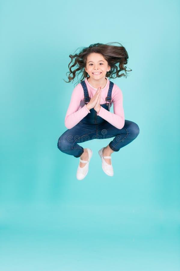 Poserar det lyckliga hoppet för den lilla flickan i yoga, energi royaltyfria foton