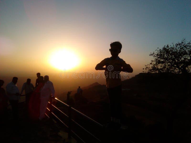 Poserar fastställd punkt för solen med trevligt av pojke royaltyfri bild