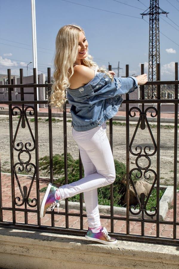 Poserar härliga unga blonda leenden för en kvinna, ställningar vid staketet, och beautifully arkivfoton