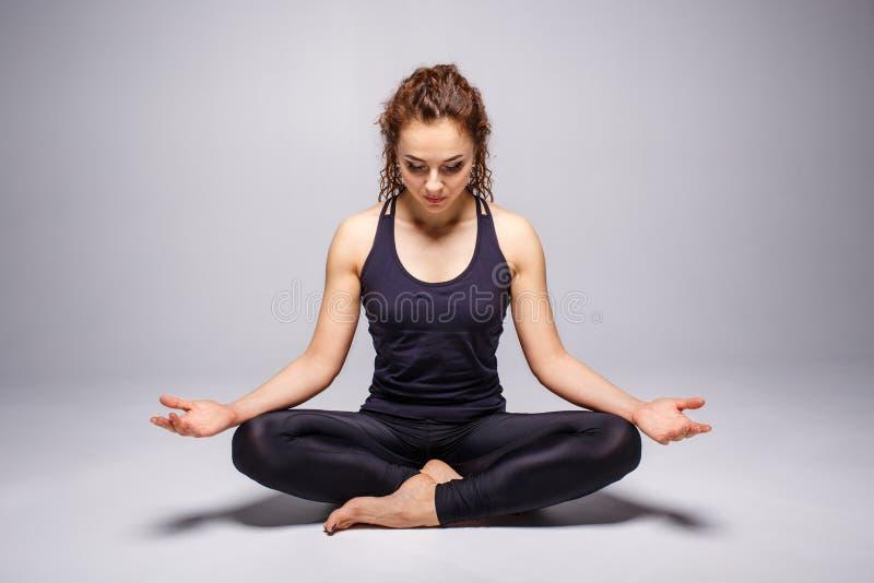 Poserar perfekt praktiserande yoga för den unga kvinnan eller lotusblomma arkivbild