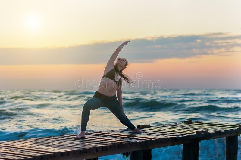 Poserar praktiserande krigareyoga för kvinna utomhus över havet eller havet och solnedgånghimmelbakgrund royaltyfri fotografi