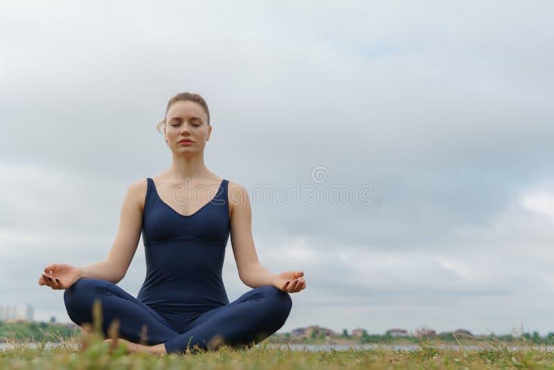 Poserar praktiserande yoga för den unga attraktiva flickan som sitter i den halva Lotus övningen, Ardha Padmasana royaltyfri fotografi