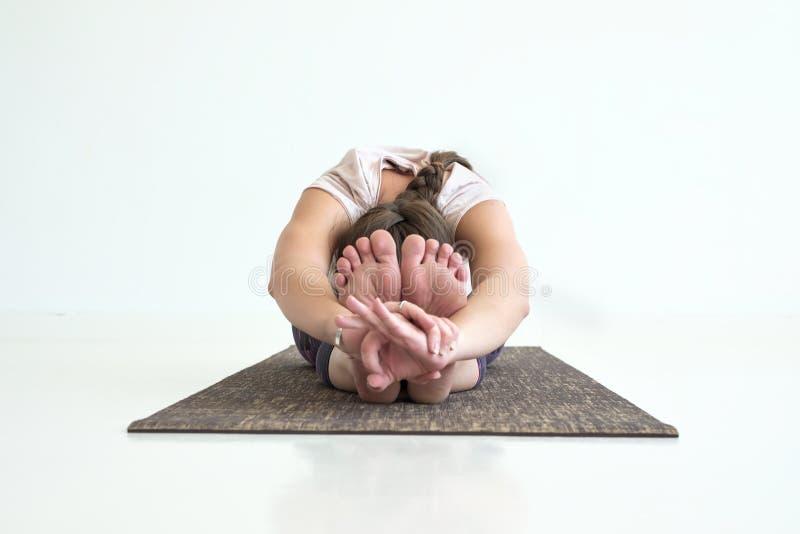 Poserar praktiserande yoga för flicka, den placerade framåtriktat krökningen och att göra paschimottanasanaövning arkivfoton