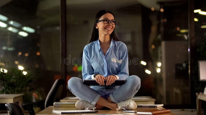 Poserar sittande lotusblomma f?r den unga kvinnliga h?llande b?rbara datorn, lyckligt med gjort arbete, framg?ng royaltyfri foto