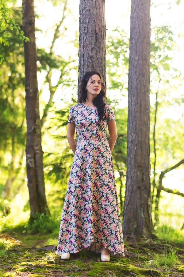 Poses bonitas novas da mulher que mostram o verão do vestido fora no por do sol fotos de stock