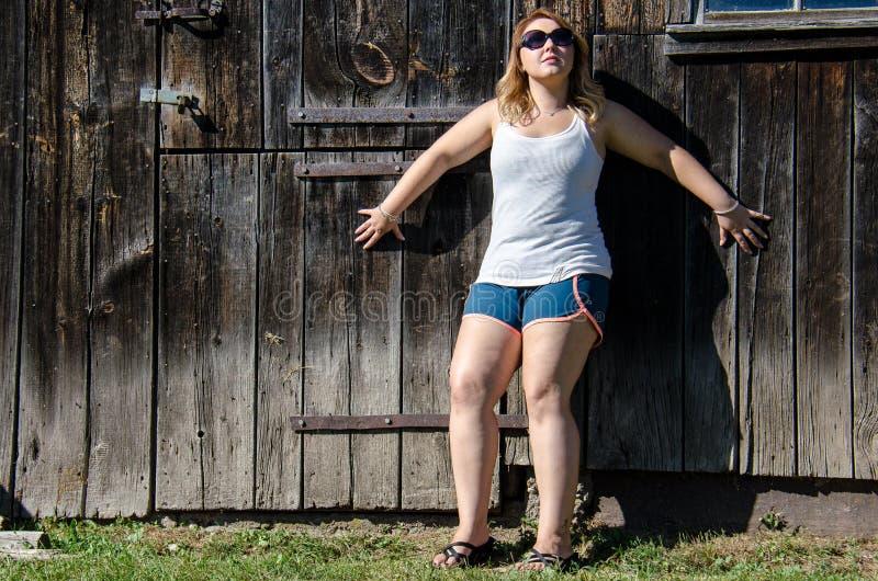 Poses de la femme 20s et modèles blonds occasionnels devant une grange en bois images stock