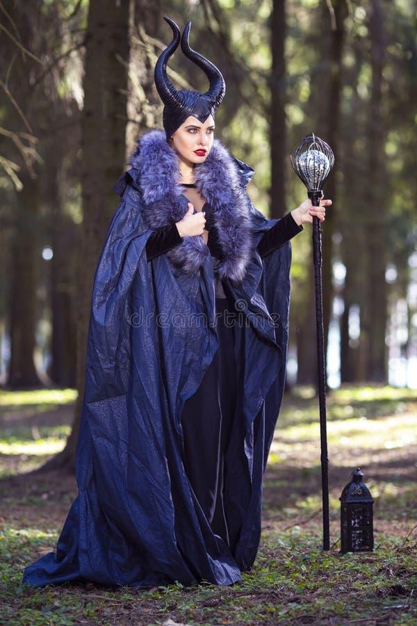 Poses f?meas caucasianos na roupa e em chifres Maleficent na mola Forest Holding Crook com bola do espelho imagem de stock royalty free