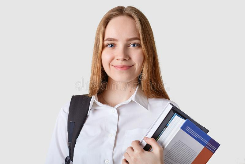 Poses fêmeas novas de cabelo louras adoráveis doces isoladas sobre o fundo branco, guardando muitos livros em ambas as mãos, olha foto de stock royalty free