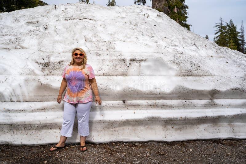 Poses louras bonitos e suportes da mulher do turista ao lado de um grande monte da neve arada no parque nacional Califórnia de La foto de stock royalty free