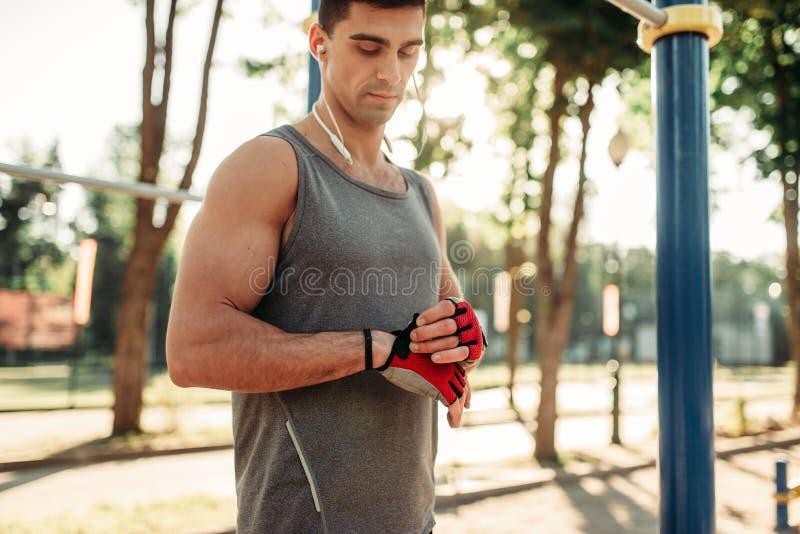 Poses masculines d'athlète sur la barre horizontale extérieure photographie stock libre de droits