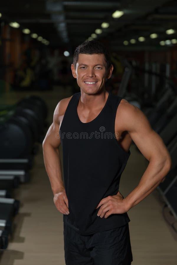 Poses musculares do atleta no gym do esporte imagem de stock royalty free