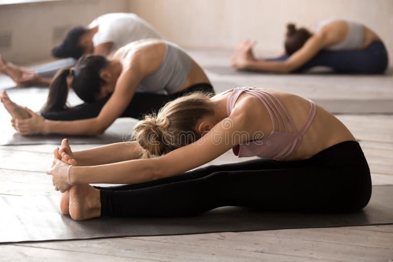 Poses novas da ioga da prática do iogue que relaxam no estúdio fotos de stock royalty free