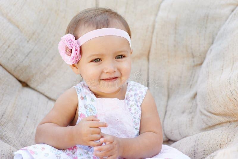 Poses pequenas do bebê em uma cadeira branca Está sorrindo felizmente imagens de stock
