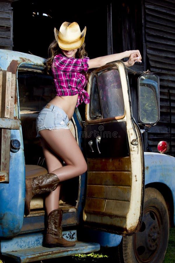 Poses sexy de cow-girl avec le vieux camion image libre de droits