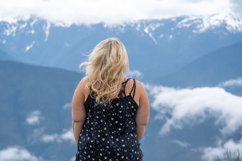 Poses vestindo da camiseta de alças da mulher loura para um retrato com as montanhas da cascata no fundo cabelo que funde no vent foto de stock