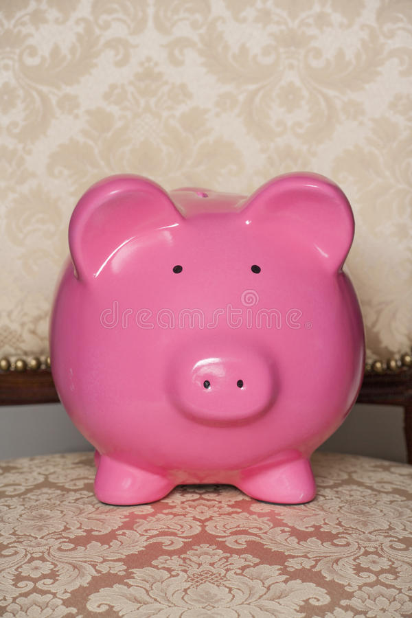 Posh piggy bank. Piggy bank on a gold floral chair royalty free stock photo