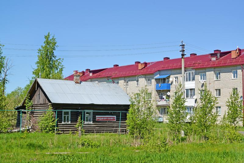 POSHEKHONJE,俄罗斯 有销售的公告的老木房子以公寓砖瓦房为背景的 免版税库存照片