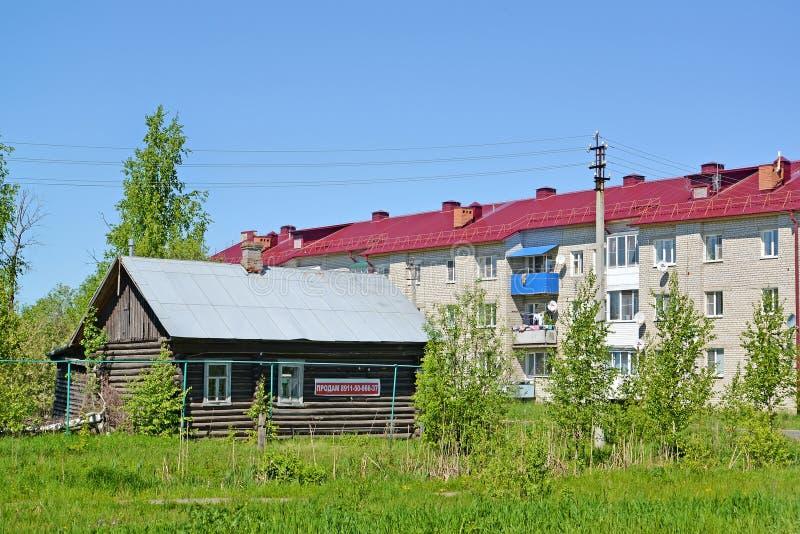 POSHEKHONJE RYSSLAND Det gamla trähuset med meddelandet av försäljningen mot bakgrunden av lägenhettegelstenbyggnaden royaltyfria foton