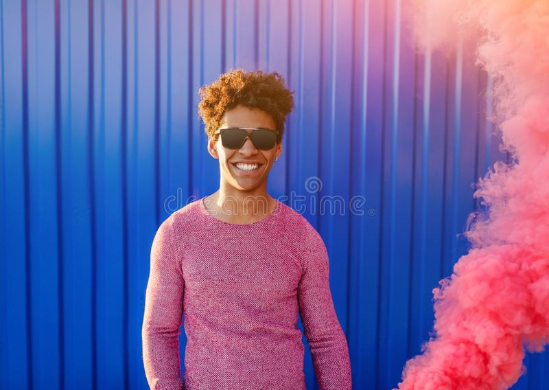 Posição à moda do homem negro no fumo colorido fotos de stock royalty free