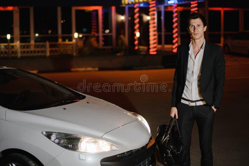 Posição à moda do homem novo ao lado de seu cabriolet branco nightlife Homem de negócios no terno no carro luxuoso imagens de stock royalty free