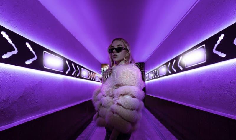 Posição adolescente da menina do moderno nas luzes de néon na rua, retrato imagens de stock royalty free