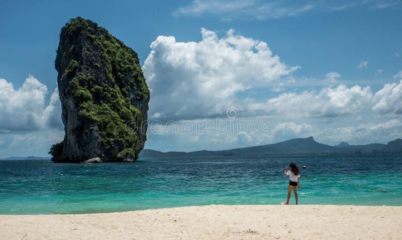 Posição adolescente da menina na praia tropical em Tailândia fotos de stock