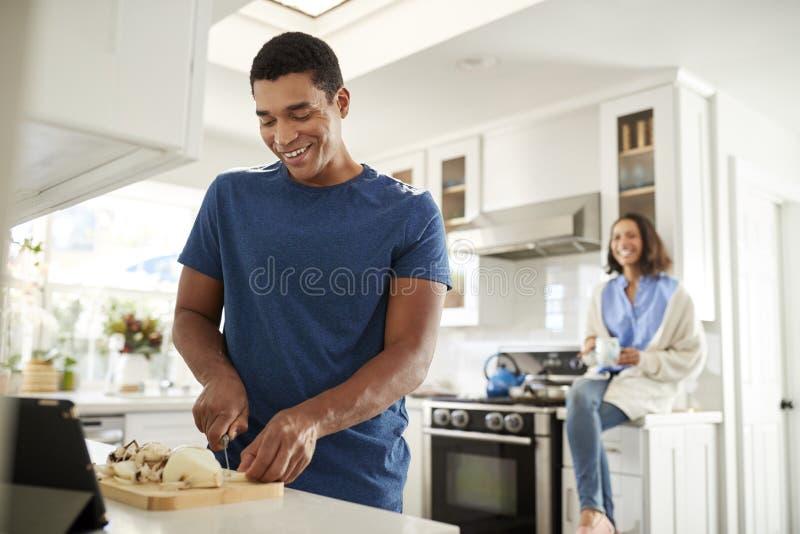 Posição adulta nova do homem na cozinha que prepara o alimento, seu sócio que senta-se no worktop da cozinha atrás dele, foco no  fotografia de stock royalty free