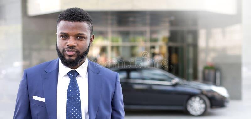Posição africana nova do homem de negócios perto do prédio de escritórios e vista da câmera fotos de stock