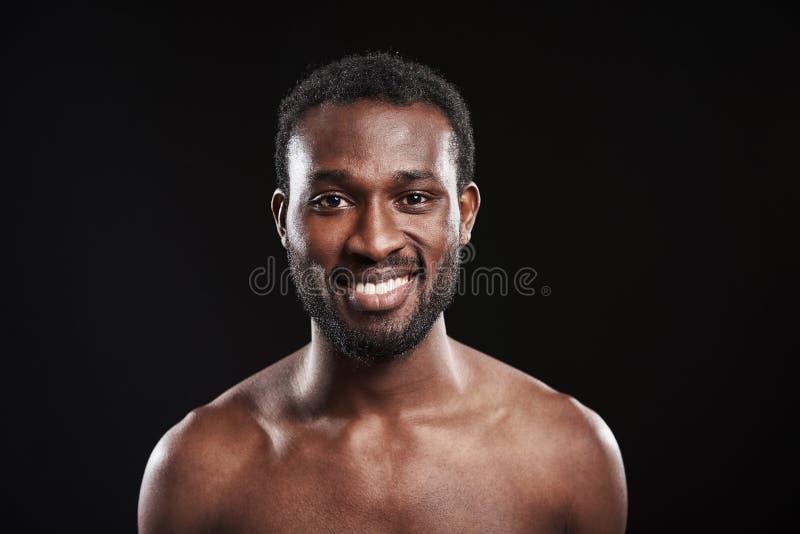 Posição afro-americana alegre do homem contra o fundo preto imagens de stock