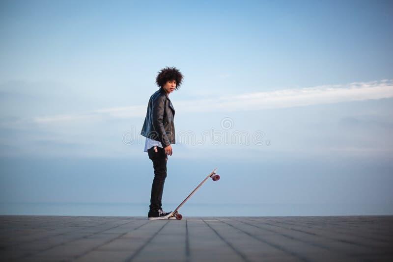 Posição afro-americana nova do homem com o skate na frente do céu azul grande fotografia de stock royalty free
