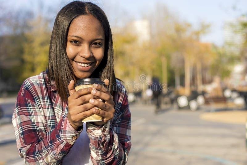 Posição afro-americano nova da mulher na rua da cidade ao guardar para levar embora o café e ao olhar a câmera em um dia ensolara fotos de stock
