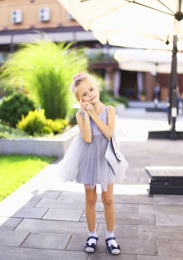 Posição agradável caucasiano pequena da menina na jarda e no vestido cinzento vestindo fotos de stock