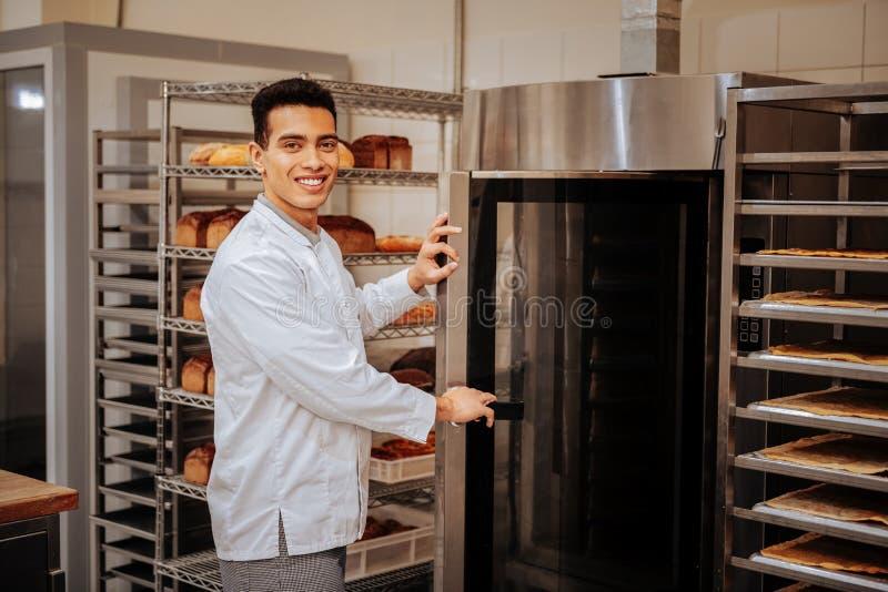 Posição agradável do padeiro perto do forno grande na cozinha imagem de stock royalty free