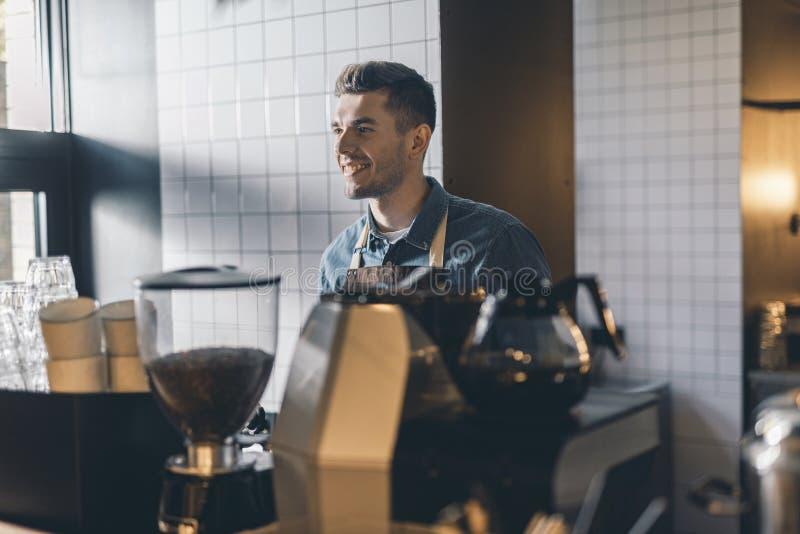 Posição alegre do barista na frente do moedor e do sorriso de café foto de stock royalty free