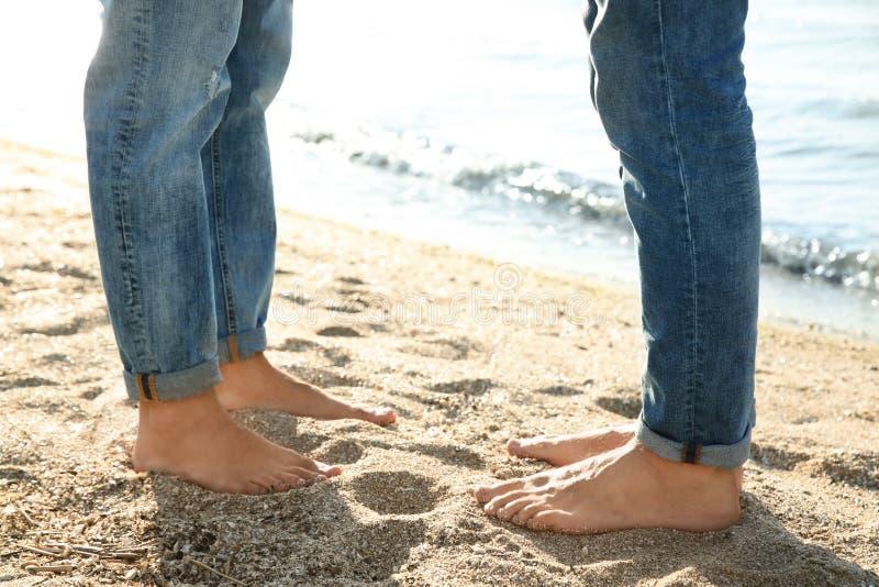 Posição alegre dos pares com os pés descalços na praia, fotos de stock royalty free