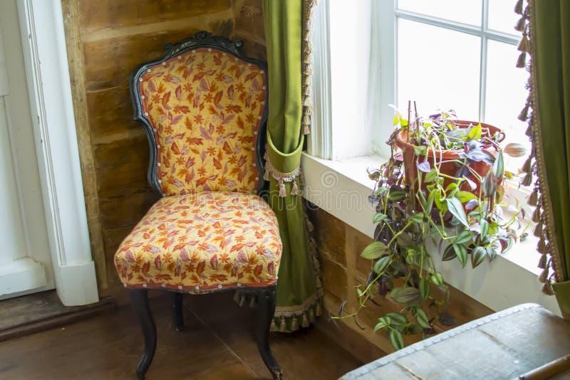 Posição antiga da cadeira no canto pela janela fotografia de stock