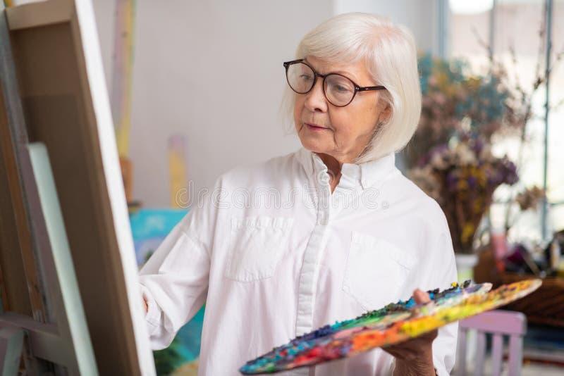 Posição aposentada talentoso da pintura da mulher perto da lona fotos de stock royalty free