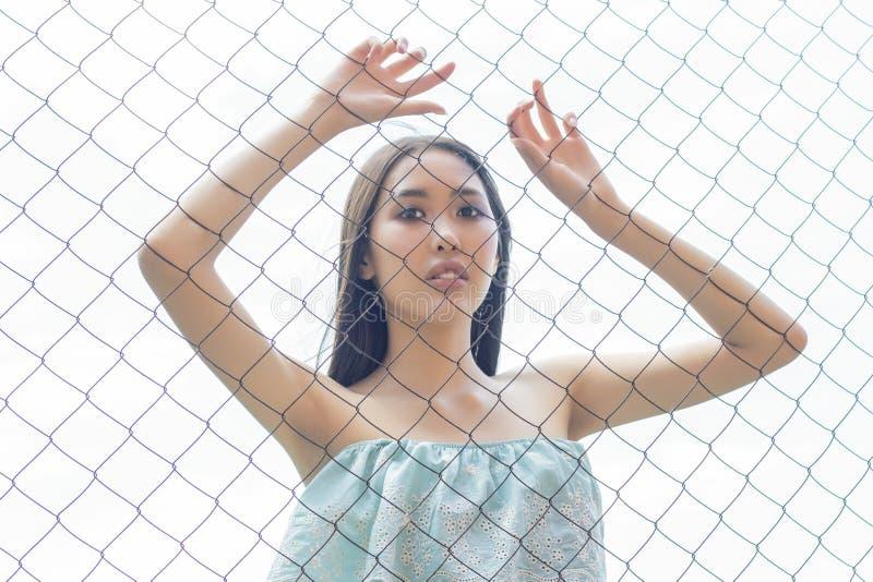 Posição asiática da menina atrás da cerca de fio em uma gaiola guardando suas mãos Conceito imagem de stock