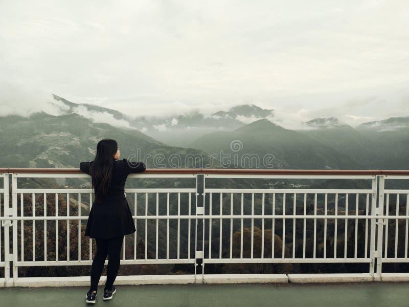 Posição asiática da mulher sozinha no balcão que examina o fundo branco nevoento e das montanhas imagem de stock royalty free