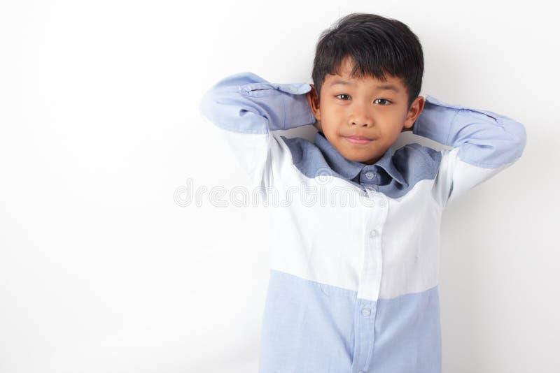 A posição asiática do menino relaxa em seu braço fotografia de stock