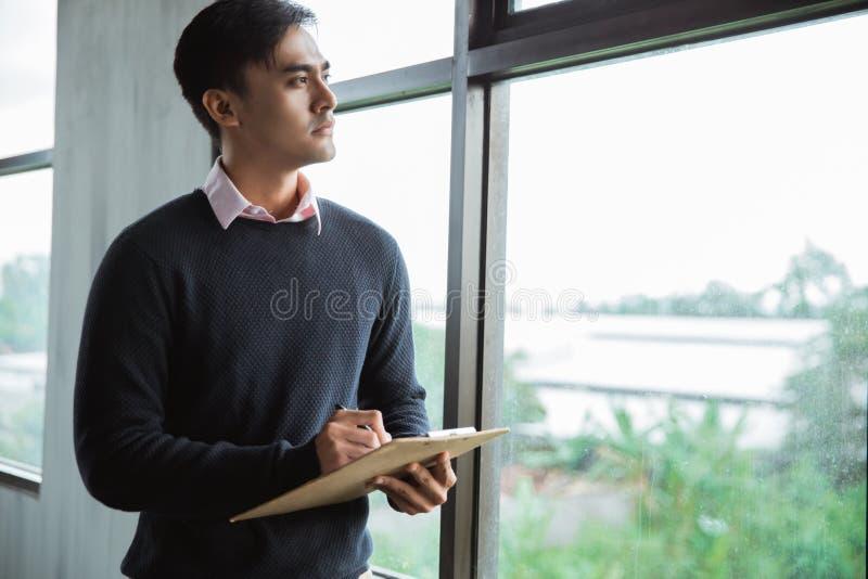 A posição asiática do trabalhador do homem escreve em uma prancheta imagens de stock