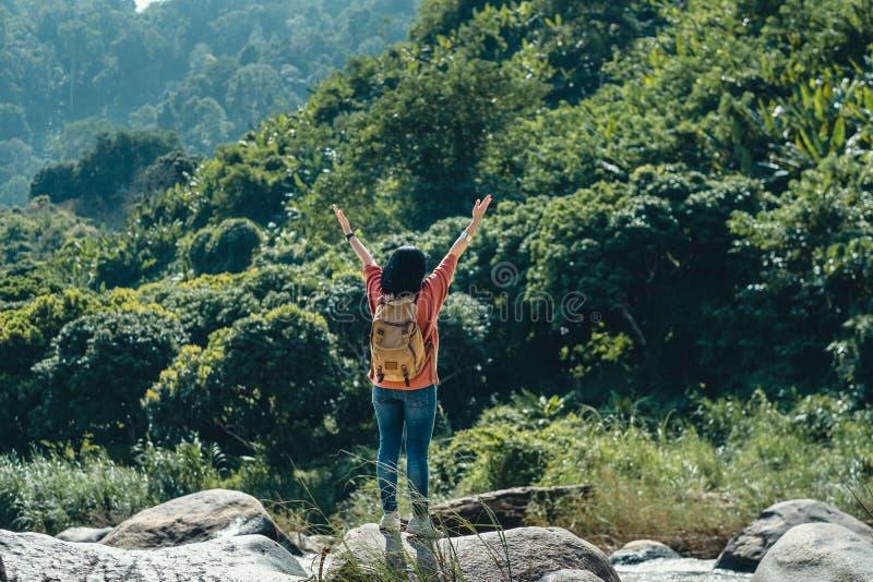 Posição asiática do viajante da mulher na rocha e nos braços acima no ar na opinião da paisagem da água verde da floresta tropica fotos de stock royalty free