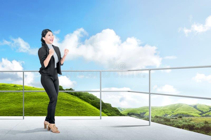 Posição asiática entusiasmado da mulher de negócio no terraço imagem de stock