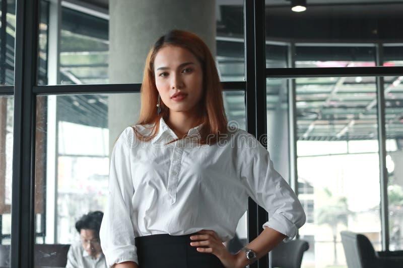 Posição asiática nova segura da mulher de negócios no escritório Pensamento e conceito pensativo do negócio imagem de stock royalty free