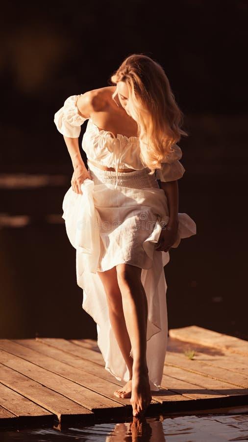 Posição atrativa da jovem mulher pelo lago no por do sol ou no nascer do sol fotografia de stock royalty free