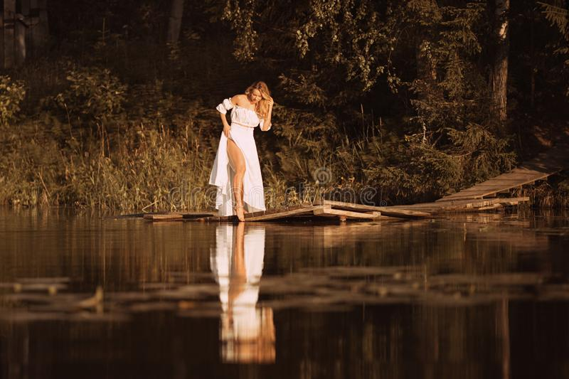 Posição atrativa da jovem mulher pelo lago que mostra seus pés 'sexy' imagem de stock