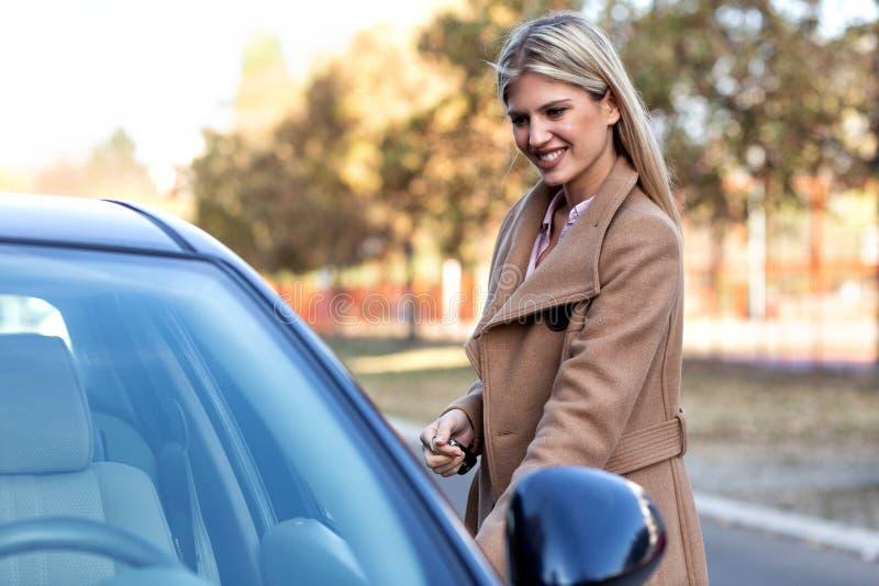 Posição atrativa da mulher na frente do carro imagens de stock