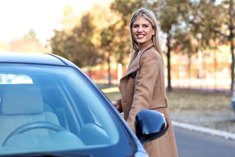 Posição atrativa da mulher na frente do carro fotos de stock