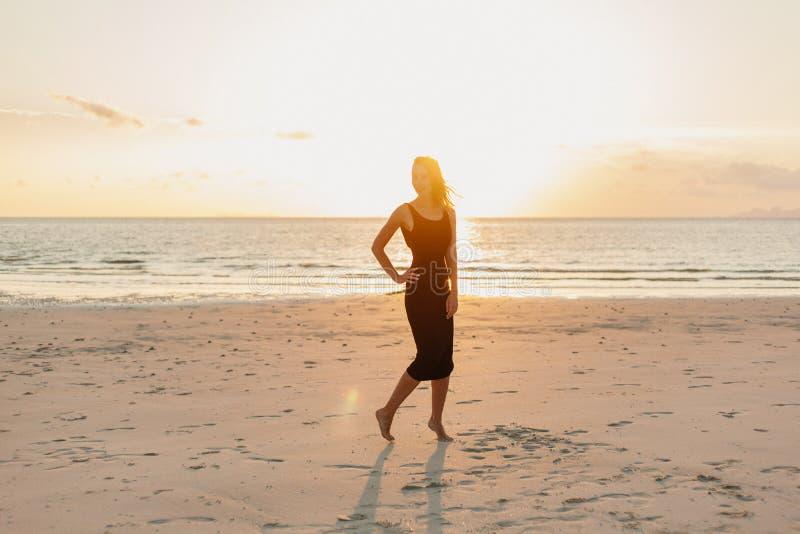 posição atrativa da mulher na praia do oceano nos raios de sol foto de stock royalty free
